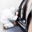 Worker painting a car in a special painting box, wearing a whitecostume and a breathing helmet as protection gear — Stock Photo