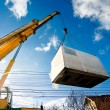 Industrial Crane operating and lifting an electric generator against sunlight and blue sky — Stock Photo #37011021