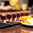 Several alcohol shots on bar with tequiland orange or lemon — Stock Photo #37072091