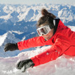 Happy girl waving on snow on the top of a mountain, with Alps background — Stock Photo