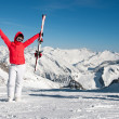 Excited girl standing on top of the mountain with skiis and sticks in her hands on a sunny winter day — Stock Photo #37076933