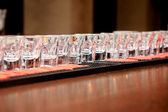 Alcoholic drink in small glasses on the bar in party nightclub waiting to be served — Stock fotografie