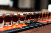 Red, strong alcoholic drink in small glasses on bar waiting to be served in a nightclub — Foto Stock