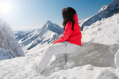 Girl resting from skiing on top of mountain, with scenic background — Stock Photo