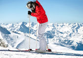 Female skier on ski slope in european alps with mountain background — Stock Photo
