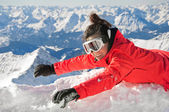 Happy girl waving on snow on the top of a mountain, with Alps background — Stockfoto