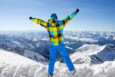 Male wearing ski equipment being excited about climbing on top of European Alps on a sunny winter day — Stock Photo