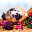 Christmas decoration with balls, flower petals and cinnamon over snowy background — Stock Photo