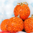 Four orange glittering christmas balls with shiny background of snowflakes — Stock Photo