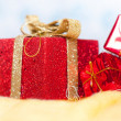 Red little shiny presents on a fluffy yellow surface isolated over white and blue background — 图库照片
