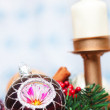 Christmas Ball with pine tree, berries and candle over a white and blue background — Stock Photo