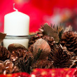 Christmas wreath with candle, cones and tinsel isolated over red background — Stock Photo