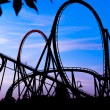 Silhouette of a roller coaster at a blue sunset during a fun fair at entartaiment thematic park — Stock Photo