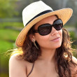 Closeup portrait of a stunningly sexy brunette woman wearing a nice summer, beach red hat and sunglasses while playing with her hair — Stock Photo