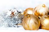 Christmas tinsel with balls and shiny background — Stock Photo