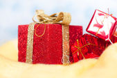 Red little shiny presents on a fluffy yellow surface isolated over white and blue background — Stock Photo