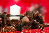 Christmas wreath with candle, cones and tinsel isolated over red background — Stockfoto