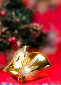 Two bell-shaped christmas balls with a christmas tree in the background — Stock Photo