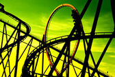 Silhouette of roller coaster against green background — Stock Photo
