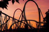 Silhouette of a roller coaster at a purple sunset during a fun fair, after a sunny day — Stock Photo