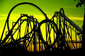 Silhouette of a roller coaster at sunset, after a sunny day — Stock Photo