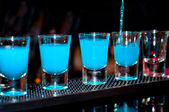 Bartender pours blue alcoholic drink into small glasses on bar with black background — Stock Photo