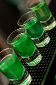 Green alcoholic liquid in shot glasses standing on the counter — Stock Photo