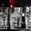 Three vodka glasses on the bar with lots of ice, waiting to be served. — Stock Photo #37170101