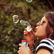 Portrait of an sexy and attractive brunette blowing bubbles in the park — Stock Photo