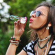 Portrait of an attractive brunette blowing bubbles in the park — Stock Photo