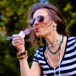 Fashion girl blowing bubbles in the wind — Stock Photo