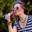 Fashion girl blowing bubbles in the wind — Stock Photo #37170151
