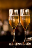 Two fancy champagne glasses in bar isolated on black background — Stock Photo
