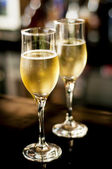 Two champagne or wine glasses against bar background — Stock Photo