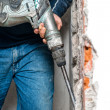 Stock Photo: Professional worker handling jackhammer and drilling into interior walls in construction site
