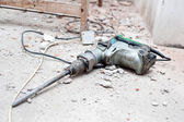 Construction tool, the jackhammer with demolition debris — Stock Photo