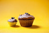 Chocolate velvet cupcake with buttercream topping and one bite cupcake isolated on yellow backround — Stock Photo