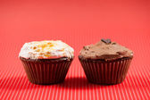 One chocolate muffin and one vanilla cupcake isolated on red background — Stock Photo