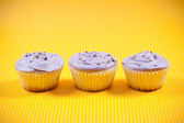 Three muffins with vanilla and chocolate filling against yellow background — Stock Photo