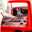 Worker painting a red car in a special garage, wearing a white costume — Stockfoto