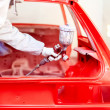 Close-up of spray paint gun with worker working on a red car — Stock Photo