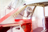 Professional mechanical engineer working in automotive industry and painting a red car — Stock Photo