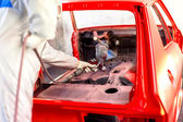 Worker painting a red car in a special garage, wearing a white costume — Stock Photo