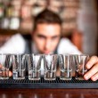 Bartender preparing and lining shot glasses for alcoholic drinks — Stock Photo #42274691