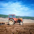 Agriculture and harvesting - Vintage tractor plowing and cultivating the field under the blue sky — Stock Photo