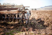 Farmer and tractor with plough, plowing in a field — Stock Photo