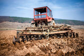 Tractor at farm working and plowing the field. Agriculture and harvesting — Stock Photo