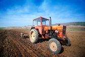 Farmer working the fields with tractor and plow — Stock Photo