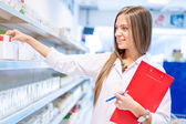 Blonde pharmacist picking medicine and drugs from shelves — Stock Photo