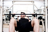 Bodybuilder training in the gym: chest - barbell incline bench press, wide grip — Stock Photo